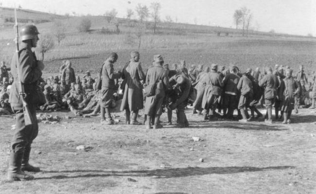 Немецкий солдат у группы югославских пленных (апрель 1941 г.).Иллюстрация: «Военный альбом»